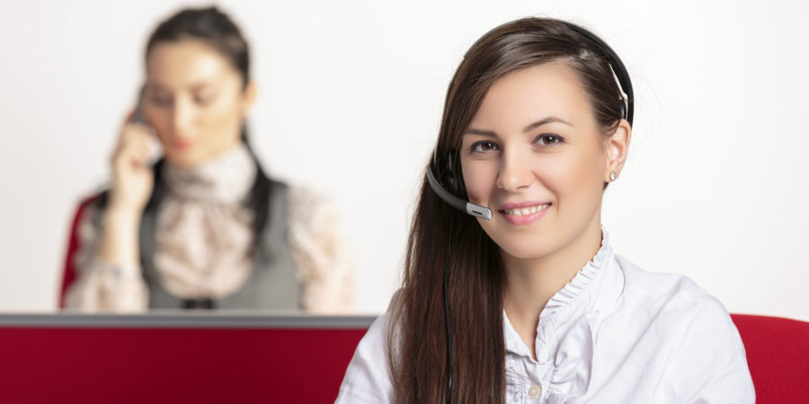 Friendly, positive female customer service representative with female colleague taking a phone call in the background.